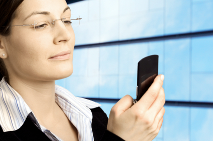 Woman with glasses reading text message